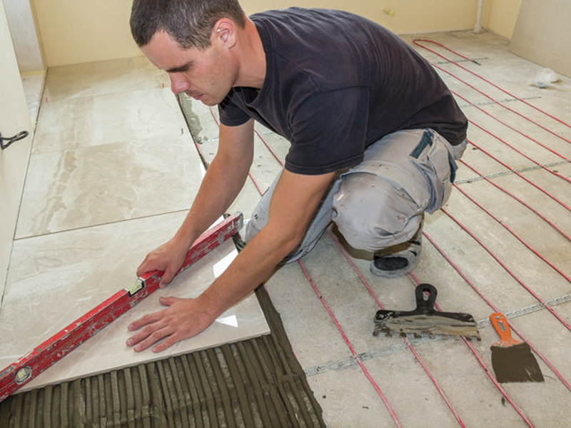 Tiler installing tiles over under floor heating in auckland